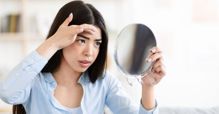 Concerned young woman looking at a growth on her forehead in the mirror.