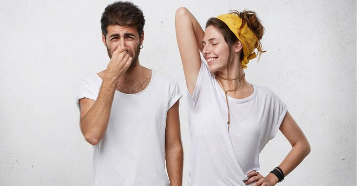 A young man blocking his nose because of the body odor coming from a young woman standing next to him