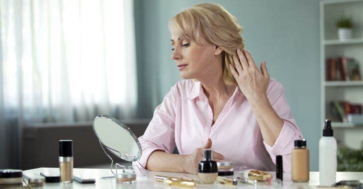 Middle-aged woman looking in the mirror to see micro-needling treatment results