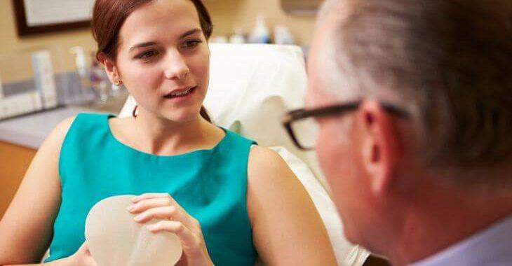 Woman and Plastic Surgeon Choosing the Right Breast Implants to Avoid Symmastia