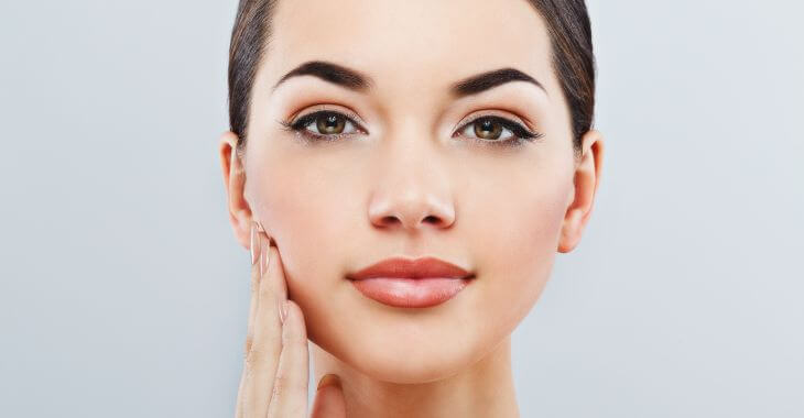Woman touching her perfect face skin after dermaplaning treatment