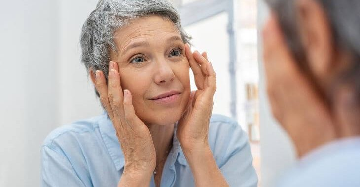 Mature woman before eye skin rejuvenation treatment looking at her face in the mirror