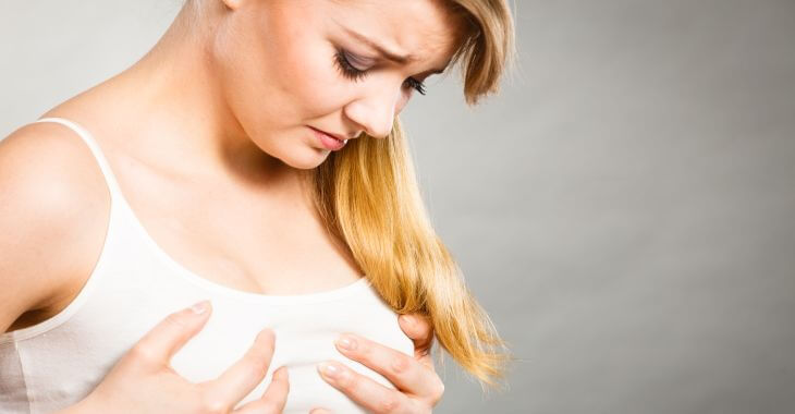 Unhappy Woman Suffering From Symmastia Looking at her Breasts