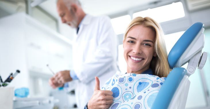 Satisfied dental patient in a dental chair during showing her thumb up