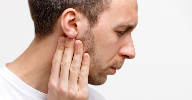 Man suffering from ear and throat pain on one side when swallowing.