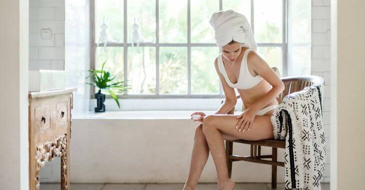 Woman in her bathroom applying a topical cream on her legs to fade dark spots.