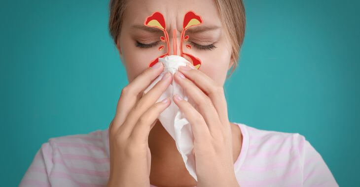 Woman with sinus infection blowing her nose.