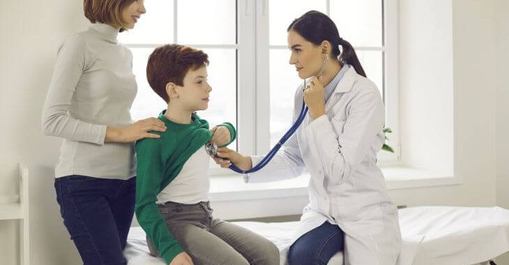 A boy assisted by his mother during doctor's appointment for precordial catch syndrome diagnosis.