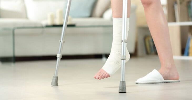 A person with leg injury walking using crutches.