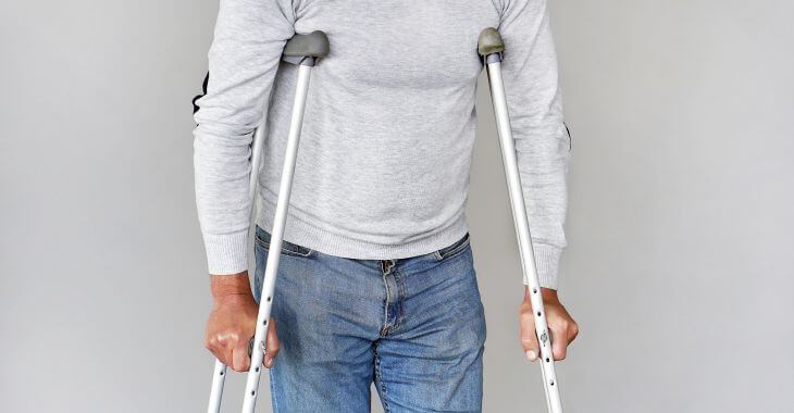 Man walking with crutches.