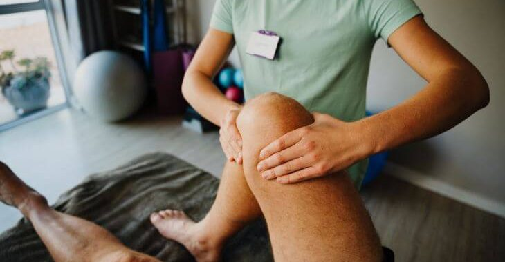 A man suffering from knee arthrosis pain during physical therapy session.