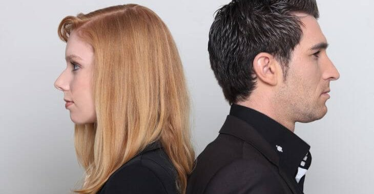 Profiles of young woman and man turned backs to each other.