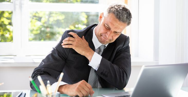 A businessman at work suffering from shoulder arthrosis pain.