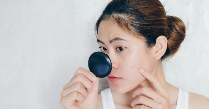 A concerned young Asian woman checking her facial skin in a mirror.