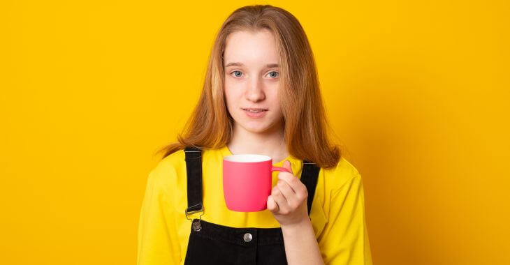 An adolescent girl with a mug of coffee.