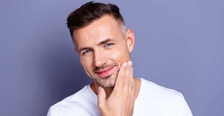 A satisfied middle-aged man after mini facelift touching the skin on his face.
