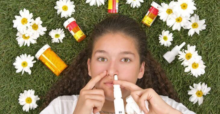 A teenage girl lying on grass among allergy medications.