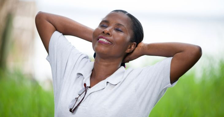 A happy Afro-American woman spending time outdoors breathing deeply fresh air.