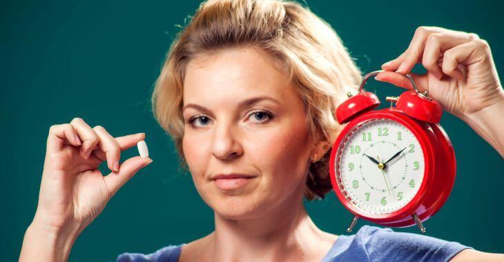 A woman holding a melatonin pill and an alarm clock.