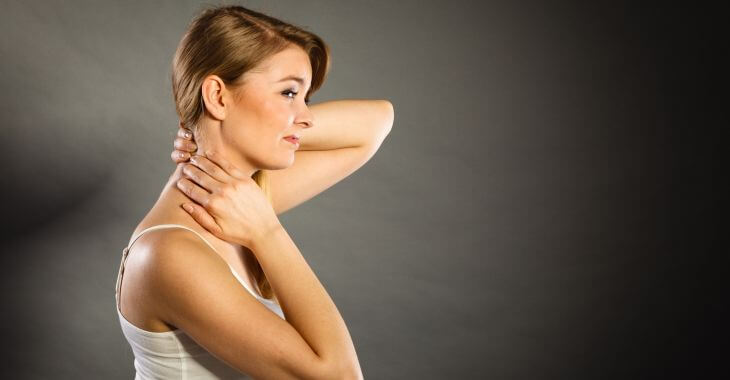 A woman touching a lump on the back of her neck.