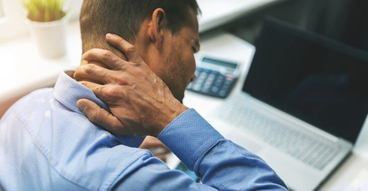 A man touching a lump on the back of his neck.