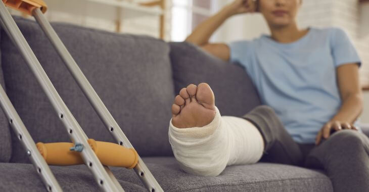 Crutches next to a woman with a broken leg in a plaster resting on a sofa.