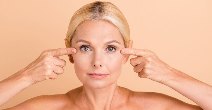 A mature woman pointing to her eyelids after non-surgical skin tightening treatment.