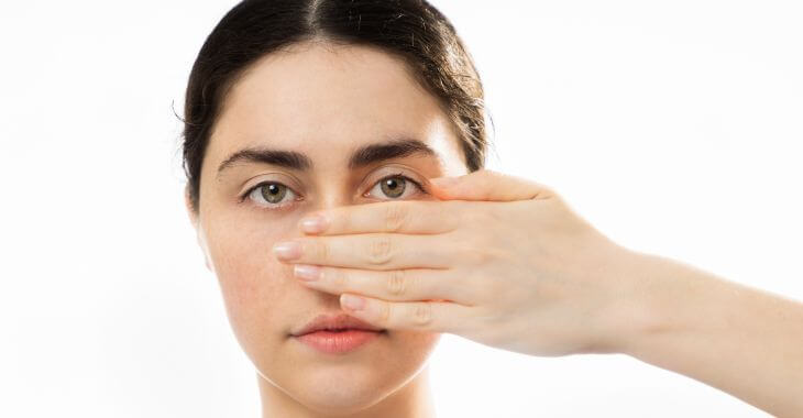 A woman covering her nose with her hand.